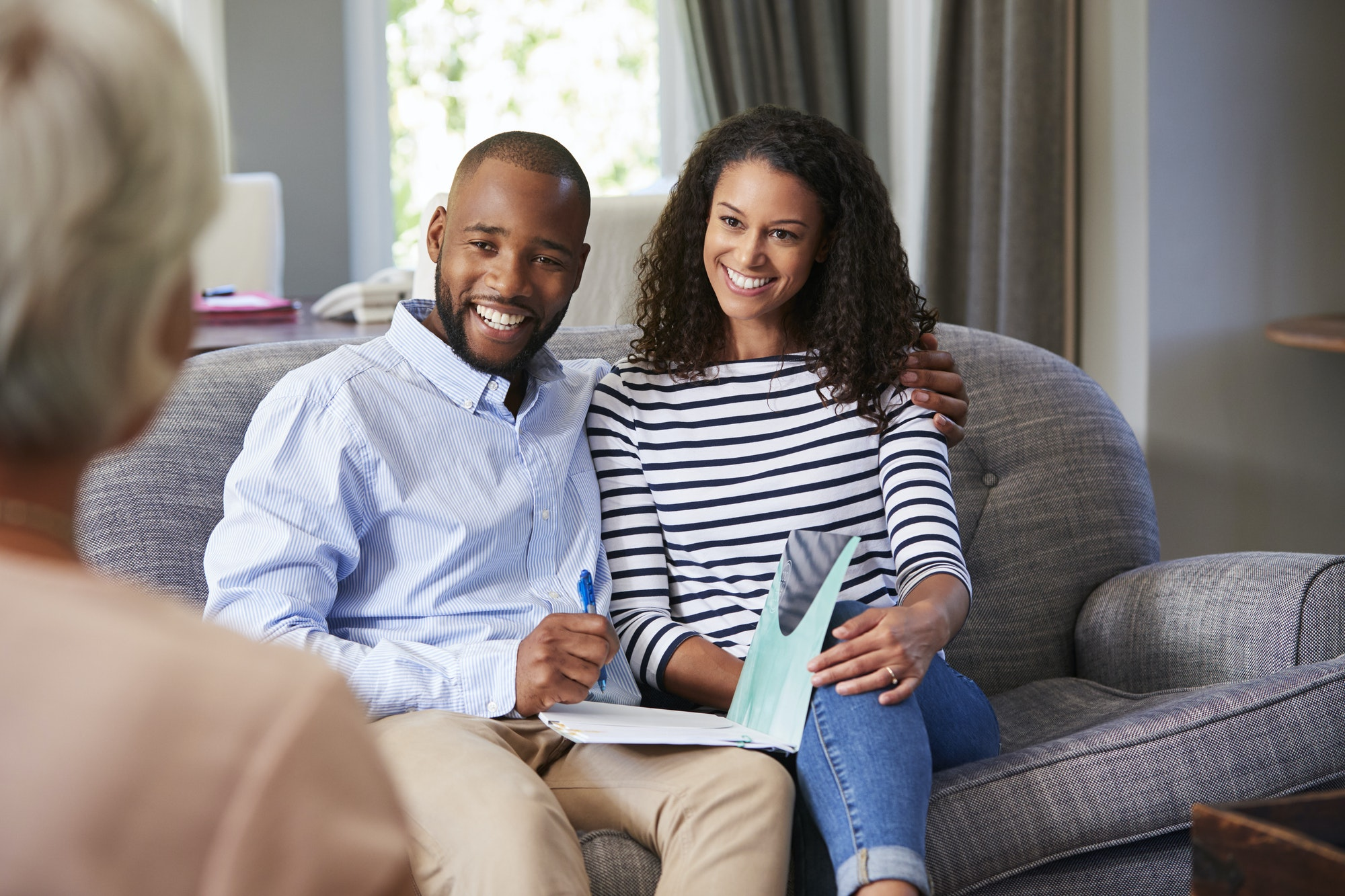 Happy young couple taking financial advice at home
